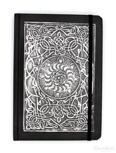 Notebook dressed in black artificial leather, decorated with aluminum plate with floral ornaments